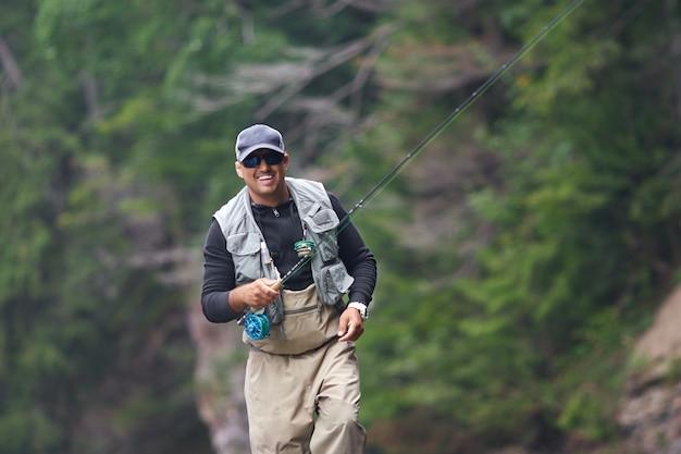Vrolijke man in pet en waterdichte outfit vissen in de ruige rivier tussen prachtige bergen. concept van vrije tijd en hobby.