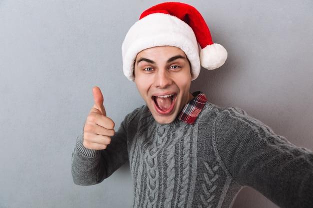 Vrolijke man in trui en kerstmuts selfie maken en duim opdagen