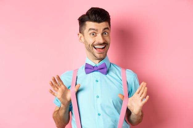 Vrolijke man in vlinderdas, die zijn bretels laat zien en gelukkig glimlacht, zich vrolijk voelt, opgewonden staat over roze achtergrond.