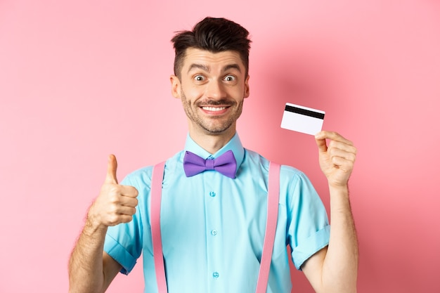 Vrolijke man in vlinderdas met duim omhoog en plastic creditcard, zoals promo-aanbieding, gelukkig glimlachend in de camera, staande over roze achtergrond.
