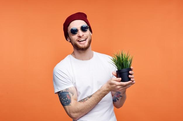 Vrolijke man in zonnebril met een bloem oranje achtergrond