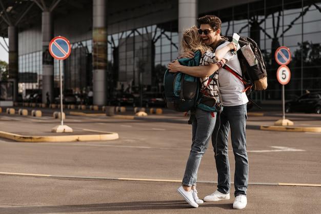 Vrolijke man in zonnebril, wit t-shirt, jeans knuffels met blonde vrouw in geruit hemd