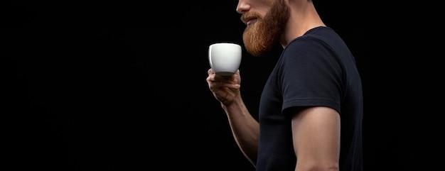 Vrolijke man in zwart t-shirt met koffiekopje drinken ochtend espresso koffie staande op zwarte achtergrond. bebaarde man die hete koffie of thee proeft. kopieer vrije ruimte aan de linkerkant.