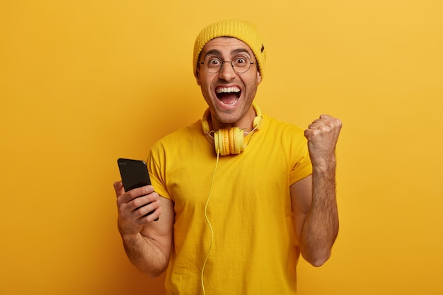 Vrolijke man juicht en viert het winnen van het smartphonegame, steekt vuist op, verheugt zich op het afronden van een moeilijk niveau, draagt stijlvolle, levendige kleding