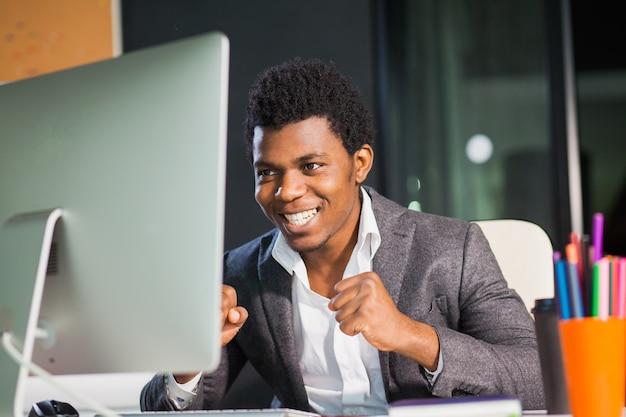 Vrolijke man kijkt gelukkig naar monitor succesvolle ondernemer freelancer kantoormedewerker