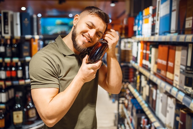 Vrolijke man knuffelt fles alcohol in supermarkt
