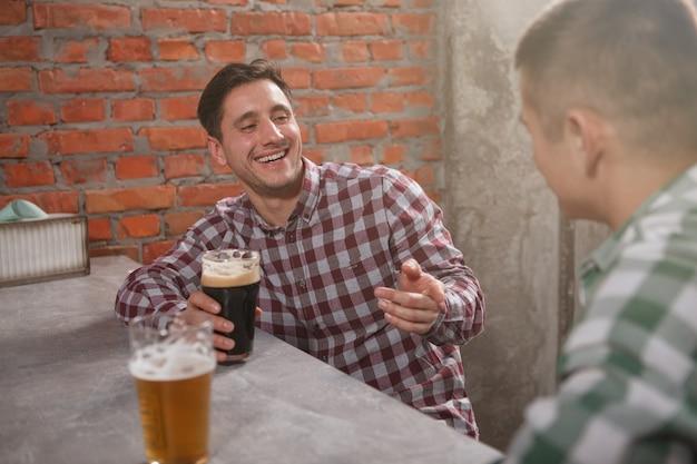 Vrolijke man lachen, praten met zijn vriend over glas bier