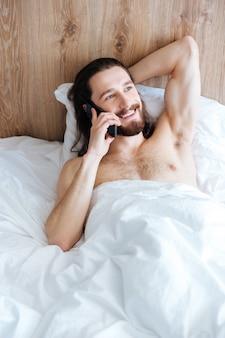 Vrolijke man liggend in bed en praten op mobiele telefoon