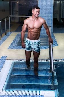 Vrolijke man lopen in het zwembad