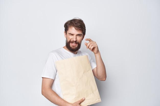 Vrolijke man met baard papieren ambachtelijke tas verpakking winkelen. hoge kwaliteit foto