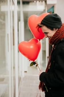 Vrolijke man met ballonnen en rozen