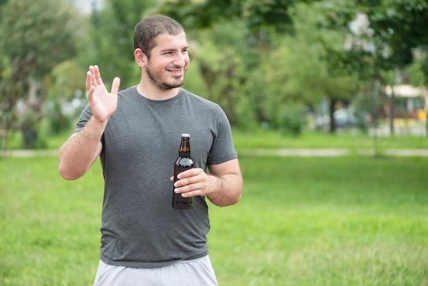 Vrolijke man met bier zwaaiende hand