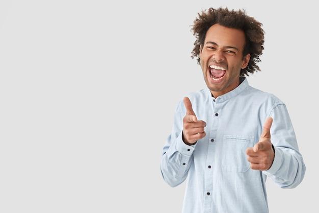 Vrolijke man met blije gezichtsuitdrukking, opent mond wijd, heeft krullend haar, geeft aan met beide wijsvingers, maakt keuze gekleed in wit overhemd vormt over muur, lege ruimte