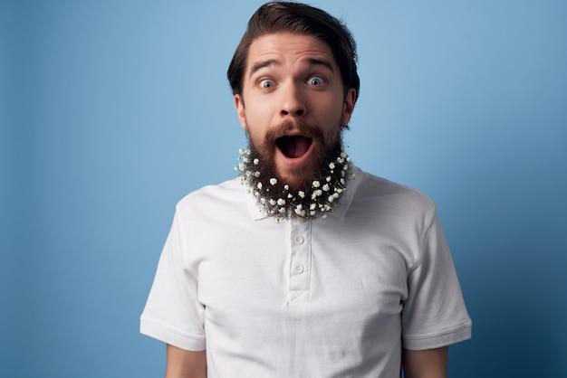Vrolijke man met bloemen in een baard haarverzorging wit overhemd blauwe achtergrond
