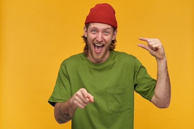 Vrolijke man met blond haar en baard. het dragen van een groen t-shirt en een rode muts. klein formaat laten zien en van je lachen, met de vinger naar je wijzend. geïsoleerd over gele muur