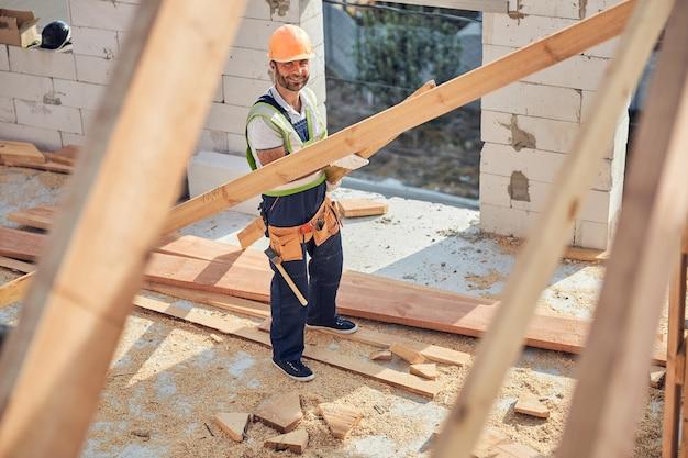 Vrolijke man met bouwuitrusting en een gereedschapsriem terwijl hij een lang stuk bouwhout vasthoudt