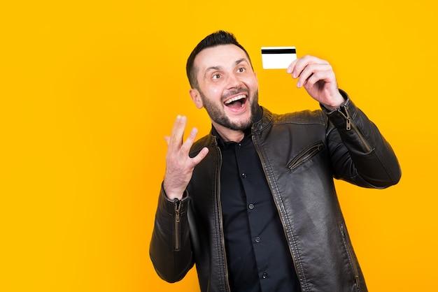 Vrolijke man met een bankkaart in zijn hand en ernaar kijken op geel