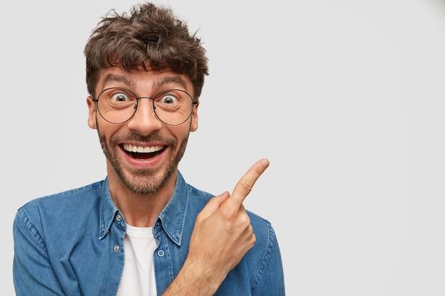 Vrolijke man met een brede glimlach, heeft een grappige uitdrukking, wijst opzij, adverteert met iets geweldigs