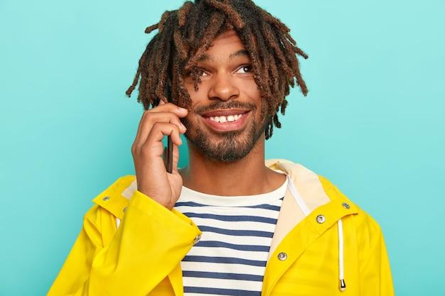 Vrolijke man met het uiterlijk van een gemengd ras, maakt telefoontje, bespreekt toekomstige reis met vriend, glimlacht breed, draagt gele regenjas
