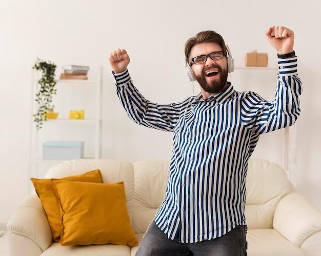 Vrolijke man met koptelefoon genieten van muziek