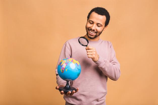 Vrolijke man met lens die de wereldbol met liefde en zorg vasthoudt die over beige wordt geïsoleerd