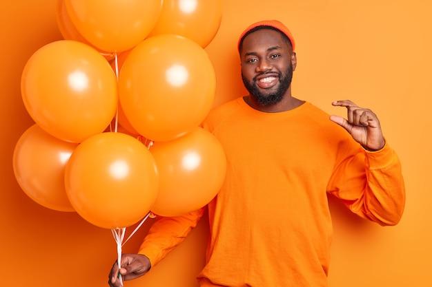 Vrolijke man met opgeblazen ballonnen maakt een klein gebaar en zegt dat hij niet veel tijd nodig heeft om zich voor te bereiden op een feest, gekleed in vrijetijdskleding die over de feloranje muur wordt geïsoleerd