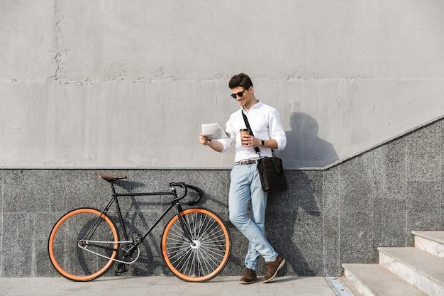 Vrolijke man met zonnebril, afhaalkoffie drinken en krant lezen, terwijl hij met de fiets langs de muur buiten staat