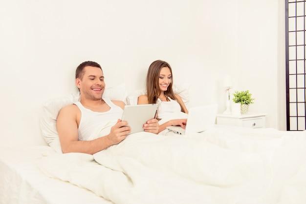 Vrolijke man nieuws op tablet lezen en zijn vrouw die op laptop werkt