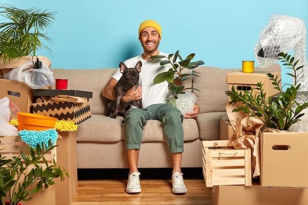 Vrolijke man omhelst hond en pot met kamerplant, zit in de woonkamer op de bank