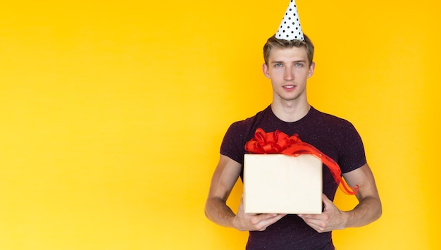 Vrolijke man op een gele achtergrond met een feestelijke pet op zijn hoofd. houdt een doos met een geschenk in zijn handen. ruimte kopiëren
