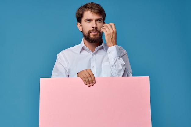 Vrolijke man roze banner in de hand blanco blad presentatie blauwe achtergrond. hoge kwaliteit foto