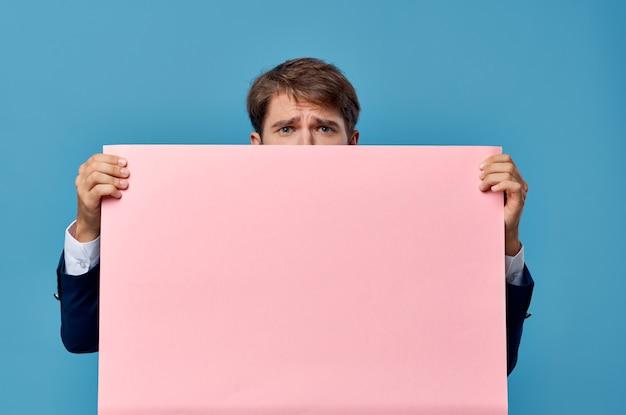 Vrolijke man roze banner in de hand blanco blad presentatie kopie-ruimte studio. hoge kwaliteit foto