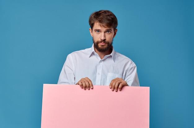 Vrolijke man roze papier in de handen van marketing leuke levensstijl blauwe achtergrond