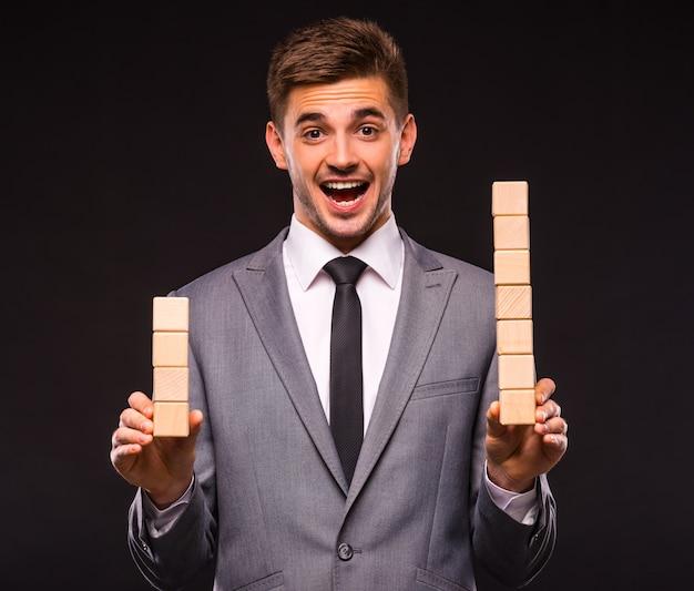 Vrolijke man staat in een pak en houdt houten kubussen.
