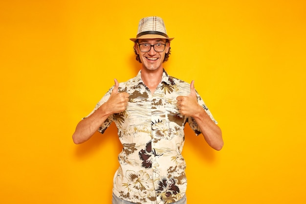 Vrolijke man toeristische reiziger geïsoleerde gele achtergrond toont gebaar met beide handen alles goed