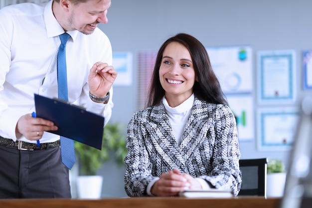 Vrolijke man toont documenten aan vrouw baas kantoor
