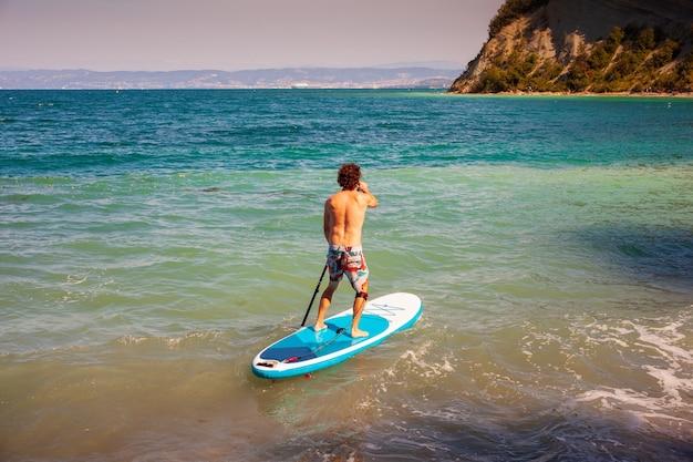 Vrolijke man traint op een zonnige ochtend een sup-bord in de adriatische zee