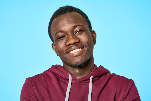Vrolijke man van afrikaanse uitstraling glimlach close-up blauwe achtergrond