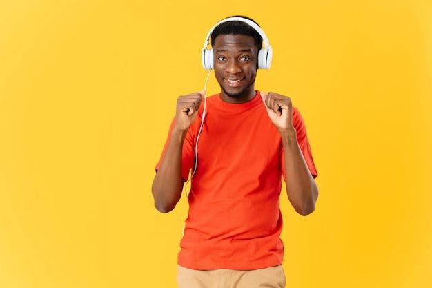 Vrolijke man van afrikaanse verschijning in hoofdtelefoons muziek entertainment gele achtergrond