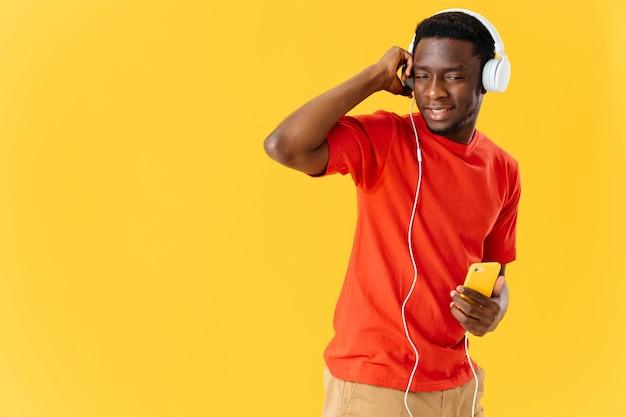 Vrolijke man van afrikaanse verschijning in hoofdtelefoons muziekentertainment
