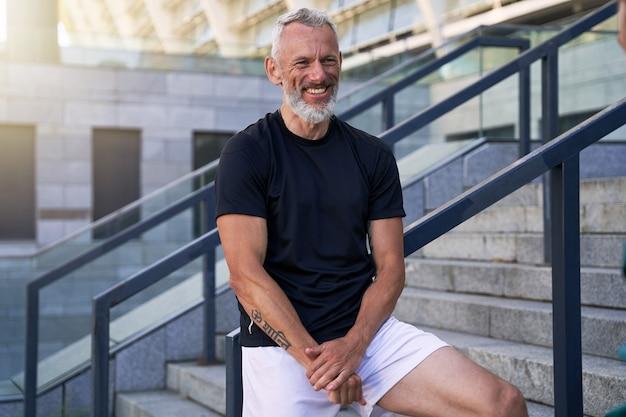 Vrolijke man van middelbare leeftijd in perfecte vorm glimlachend naar de camera terwijl hij buiten in de lucht poseert