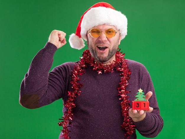 Vrolijke man van middelbare leeftijd met kerstmuts en klatergoud slinger om nek met glazen kerstboom speelgoed met datum te houden