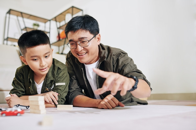 Vrolijke man van middelbare leeftijd spelen met zoon met speelgoedauto's en houten blokken wanneer hij op de vloer ligt in de speelkamer