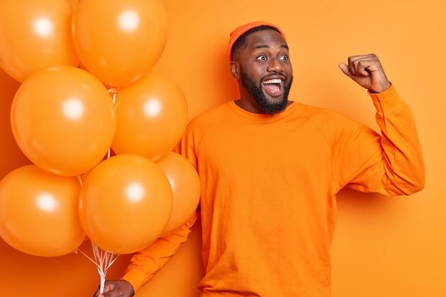 Vrolijke man voelt zich als winnaar steekt zijn arm op gebalde vuist kijkt vrolijk opzij viert het krijgen van een nieuwe baan op het werk op bedrijfsfeest houdt bos opgeblazen ballonnen staat binnen