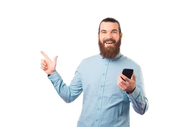 Vrolijke man wijst op de witte achtergrond terwijl hij zijn telefoon vasthoudt.