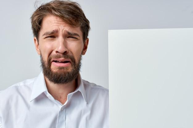 Vrolijke man witte banner in de hand blanco vel presentatie witte achtergrond