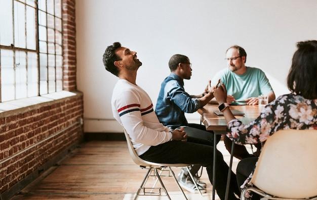 Vrolijke man zit met zijn ogen dicht in een vergadering
