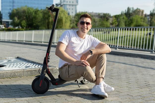 Vrolijke man zit op een elektrische scooter in een park