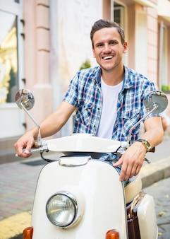 Vrolijke man zit op een scooter en kijkt naar de camera.