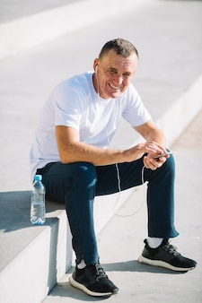 Vrolijke man zitten met een smartphone in zijn handen